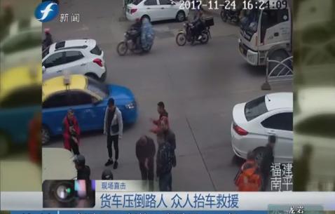 货车压倒路人 众人抬车救援