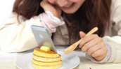 吃饭时玩手机易发胖