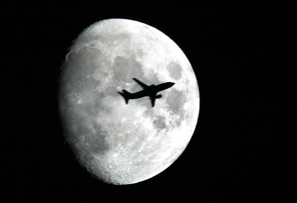 2004年10月24日,上海,一架民航从月亮表面飞过