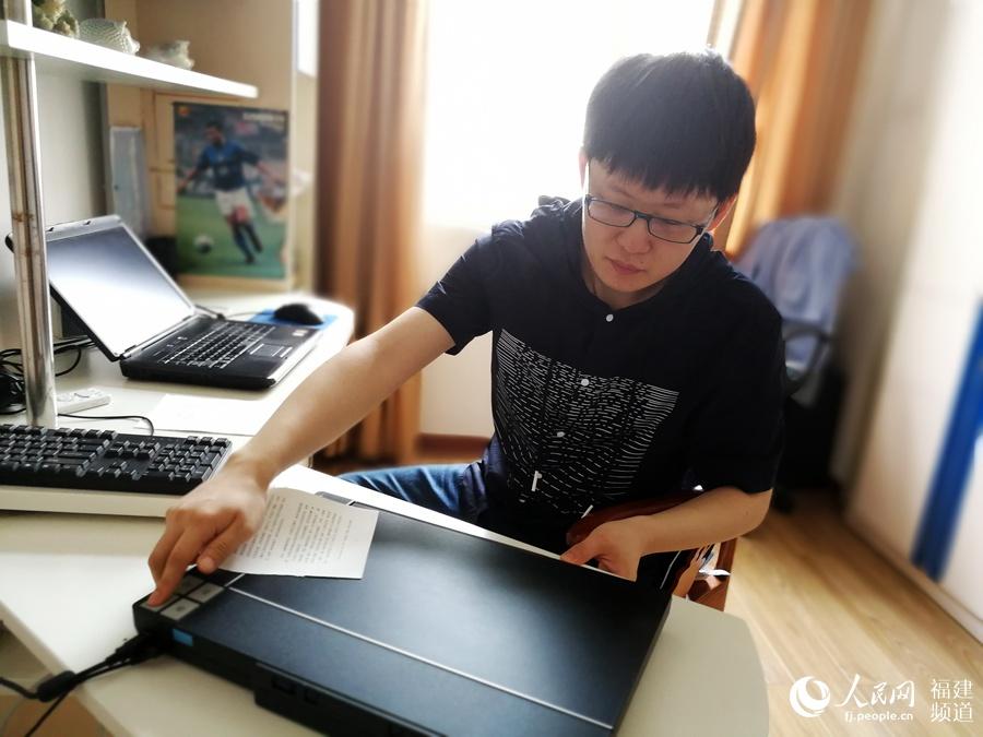 """吴可彦看书要一页页撕开扫描,变成电子书""""听""""。"""