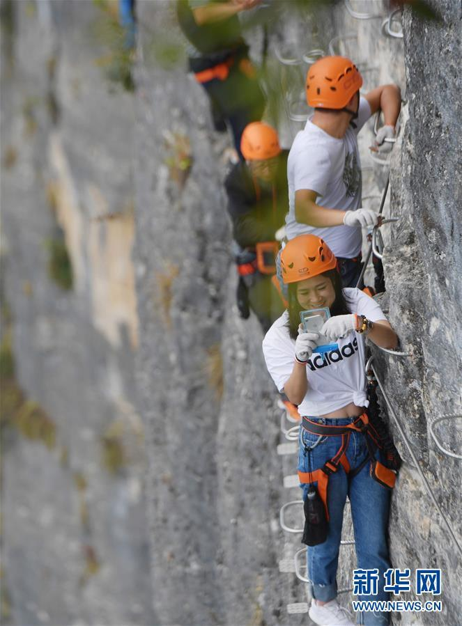 9月11日,户外运动爱好者在鸡公岭飞拉达攀岩户外运动基地攀岩。 鸡公岭飞拉达攀岩户外运动基地位于湖北省恩施土家族苗族自治州建始县花坪镇境内,拥有三条长为650米、850米、900米的攀岩线路,垂直距离距江面约500多米,吸引了众多爱好者前来体验。 新华社发(杨顺丕 摄)