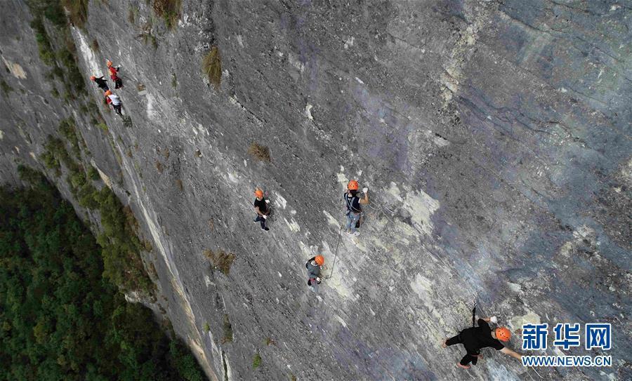 9月11日,户外运动爱好者在鸡公岭飞拉达攀岩户外运动基地攀岩(无人机拍摄)。 鸡公岭飞拉达攀岩户外运动基地位于湖北省恩施土家族苗族自治州建始县花坪镇境内,拥有三条长为650米、850米、900米的攀岩线路,垂直距离距江面约500多米,吸引了众多爱好者前来体验。 新华社发(杨顺丕 摄)
