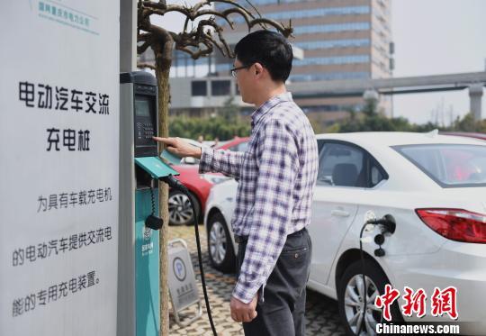资料图:重庆市民在充电桩上为电动汽车充电。 周毅 摄
