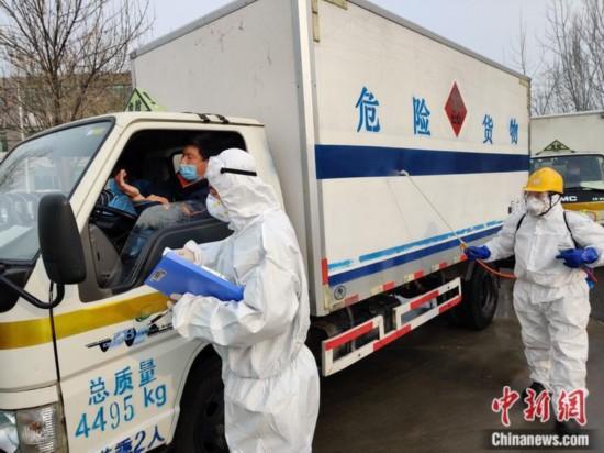 2月7日,医废转运人员在进厂前进行登记并测量体温,消毒人员对车体进行消毒处理。北京润泰环保科技有限公司 供图